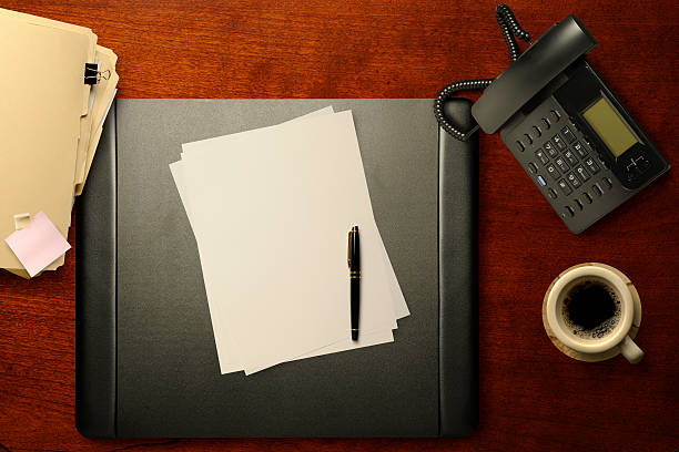 Office Chores Overhead View of Blank Writing Paper and Pen on Desk Pad with Phone, Coffee Cup, and File Folders. blotter stock pictures, royalty-free photos & images