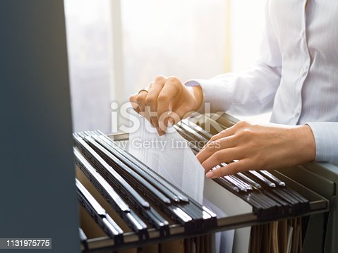 535191355istockphoto Office clerk searching files in the filing cabinet 1131975775