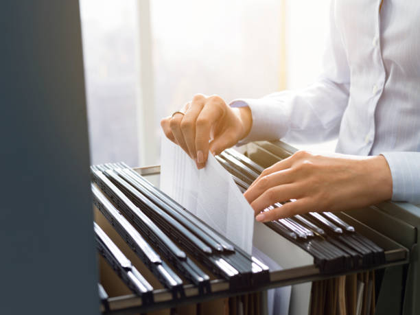 Office clerk searching files in the filing cabinet Professional female office clerk searching files and paperwork in the filing cabinet document stock pictures, royalty-free photos & images