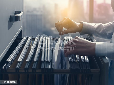 535191355istockphoto Office clerk searching files in the filing cabinet 1144836967