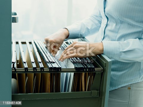 535191355istockphoto Office clerk searching files in the filing cabinet 1153461408