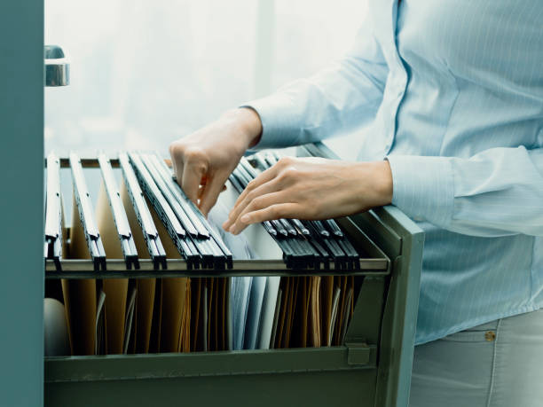 Office clerk searching files in the filing cabinet stock photo
