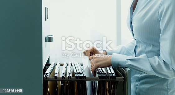 535191355istockphoto Office clerk searching files in the filing cabinet 1153461445