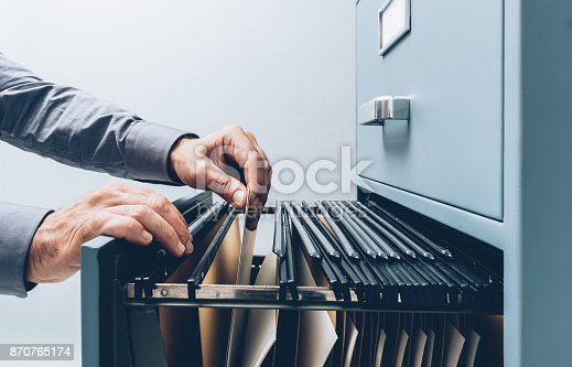 istock Office clerk searching for files 870765174