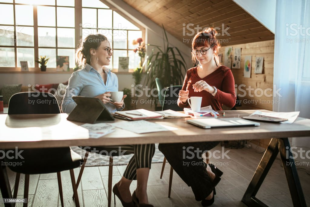 Two Female Colleagues Chatting On Coffee Break In Office