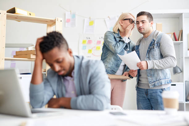 Office colleagues gossiping about new employee: attractive lady in casual clothing holding sketchpad and whispering secret to friend about failed black intern in office stock photo