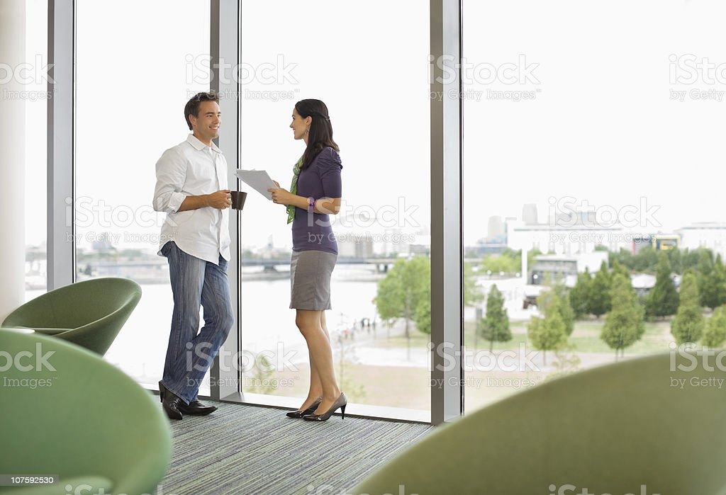 Office couple standing by bay window discussing on document in office canteen stock photo