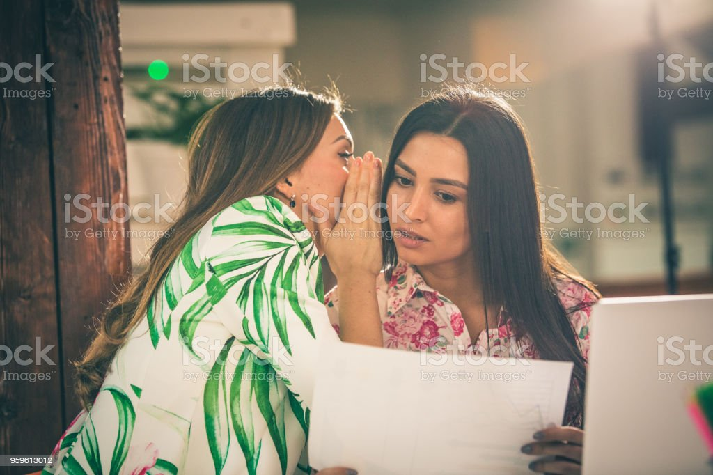 Office coworkers whispering stock photo