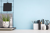 Home office creative desk with supplies, and blue wall. - Obraz