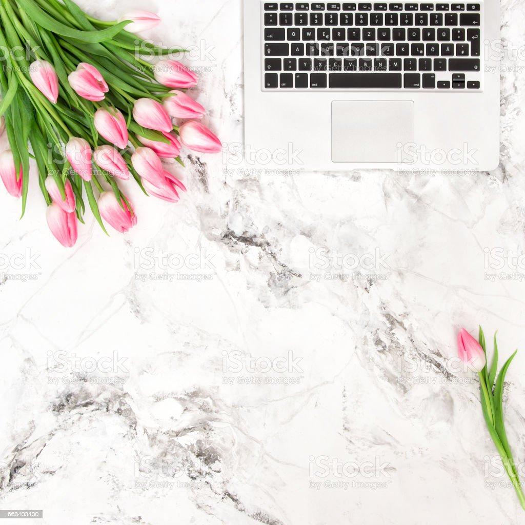 Office desk flat lay flowers Laptop tulips stock photo