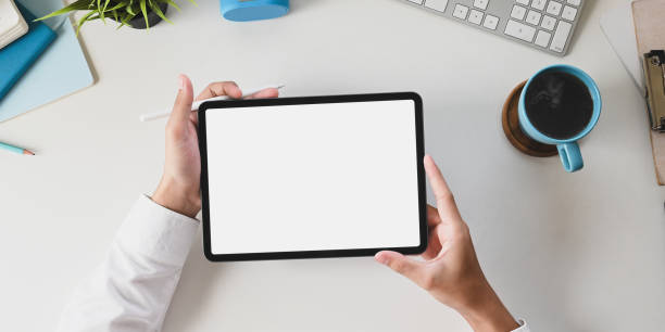 Office desk hands are holding a white blank screen computer tablet at the white working desk. stock photo