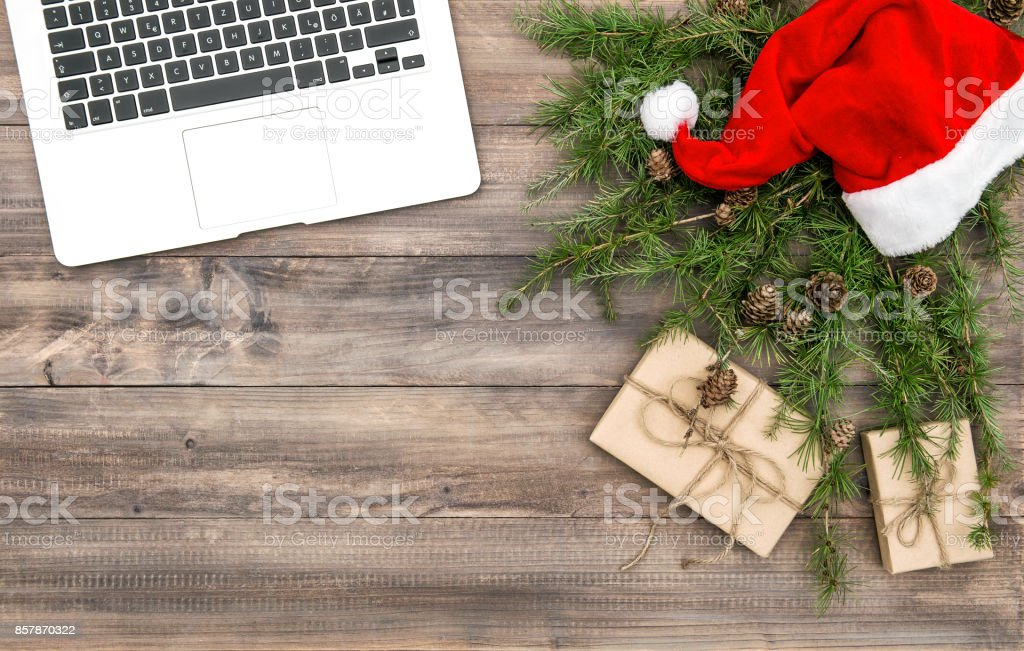Office desk laptop Christmas decoration red hat gifts stock photo