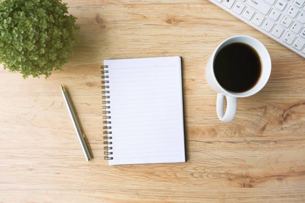 büro-schreibtisch-notizblock, stift, kaffee und computer-tastatur - schwarzer kaffee net stock-fotos und bilder