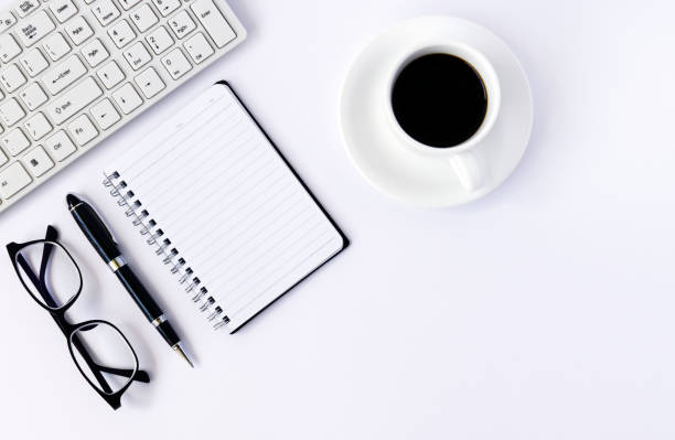 Office desk table with blank notebook page with pen, computer and cup of coffee. Top view, flat lay. stock photo