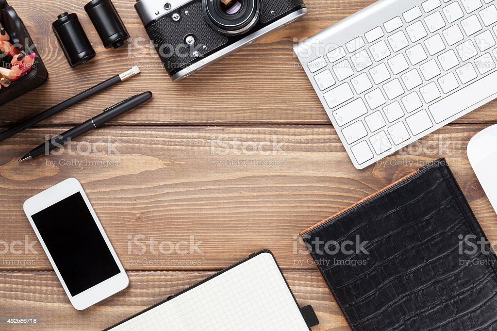 Office desk table with computer, supplies and camera stock photo