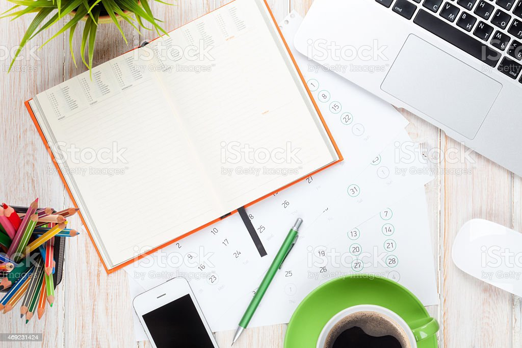Office desk table with computer, supplies, coffee cup and flower stock photo
