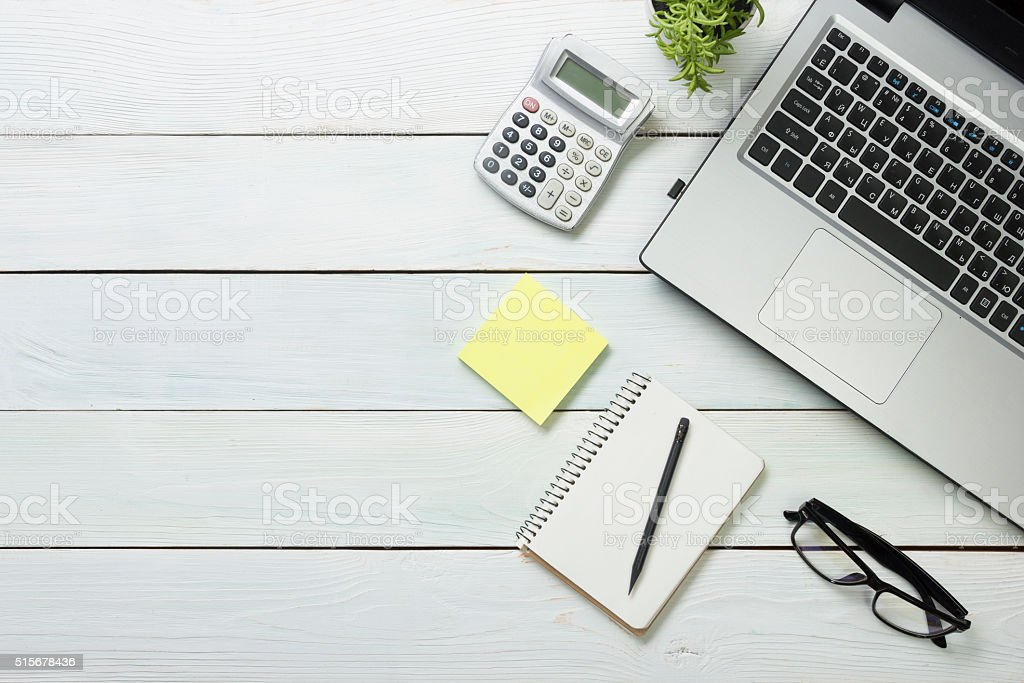 Office desk table with computer, supplies, flower. Top view. Copy stock photo