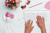 Office desk table with female hands, computer, supplies, flowers