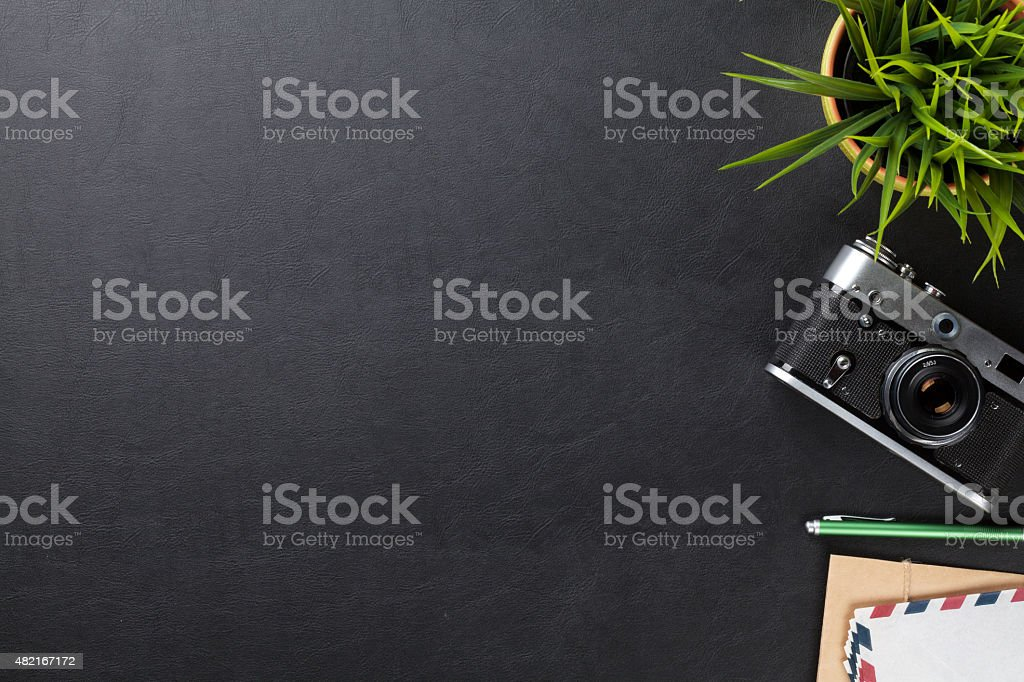 Office desk table with flower, camera and supplies stock photo