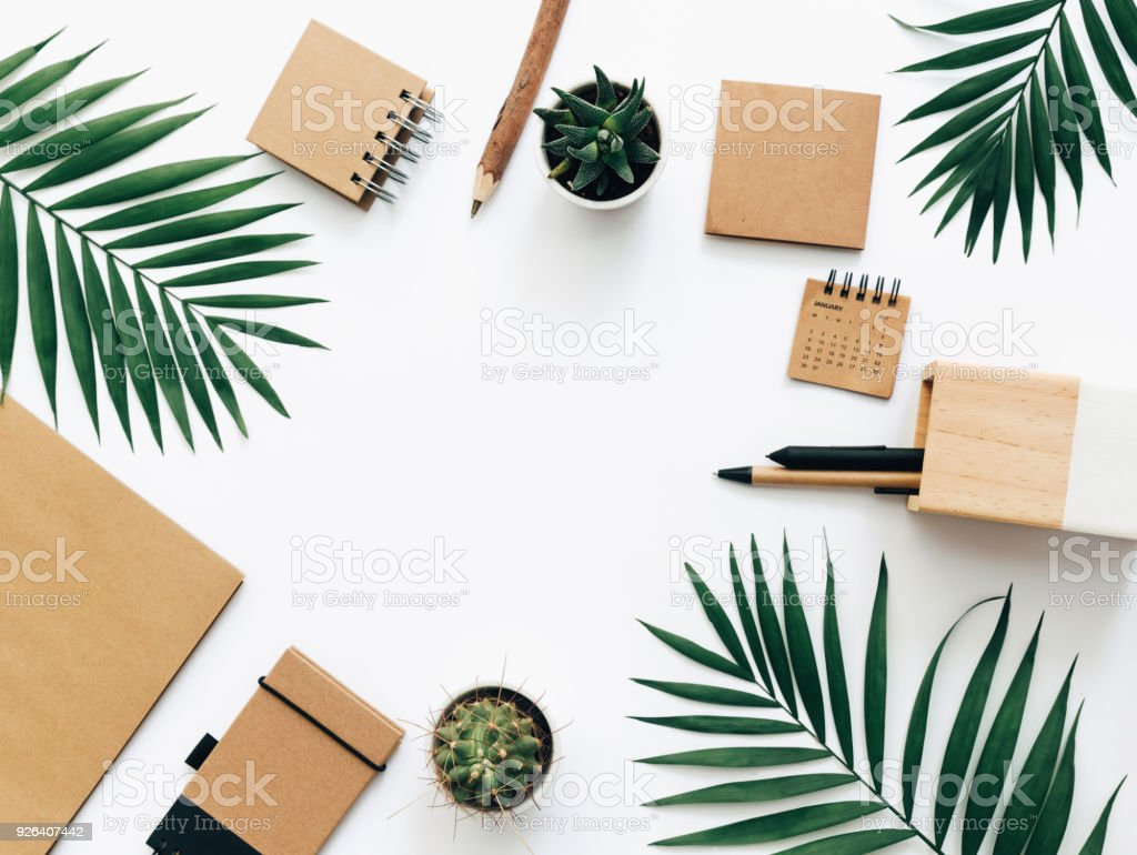 Office desk table with stationery set, supplies and palm leaves. Top view with copy space, creative flat lay. stock photo