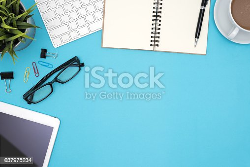 843371502 istock photo Office desk table with supplies and computer on blue background 637975234