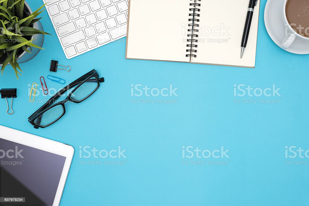 Office desk table with supplies and computer on blue background stock photo