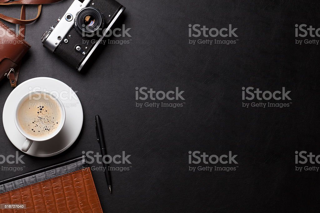 Office desk with camera, coffee and notepad