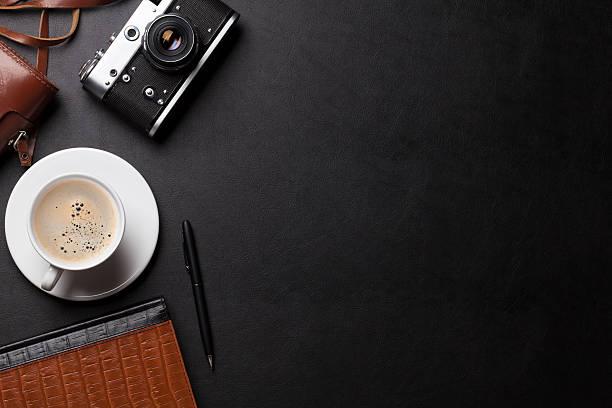 Bureau avec caméra, de café et bloc-notes. - Photo