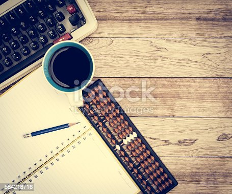 Office desk background. Coffee, notepad, pencil, abacus and typewriter on vintage wooden desk