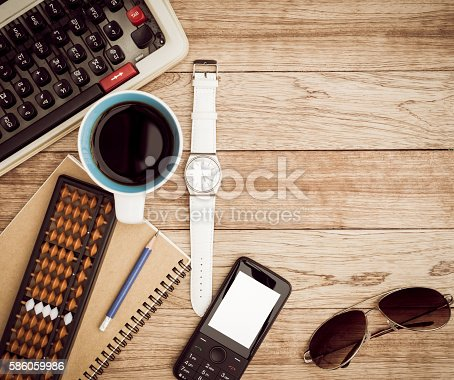 Office desk background. Coffee, notepad, pencil, wristwatch, mobile phone, sunglasses, abacus and typewriter on vintage wooden desk