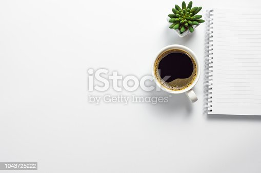 Top view of office desk with coffee cup, cactus pot and blank notebook