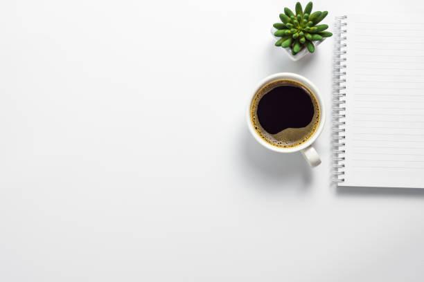 scrivania da ufficio con tazza da caffè, pentola di cactus e quaderno vuoto - flat lay foto e immagini stock