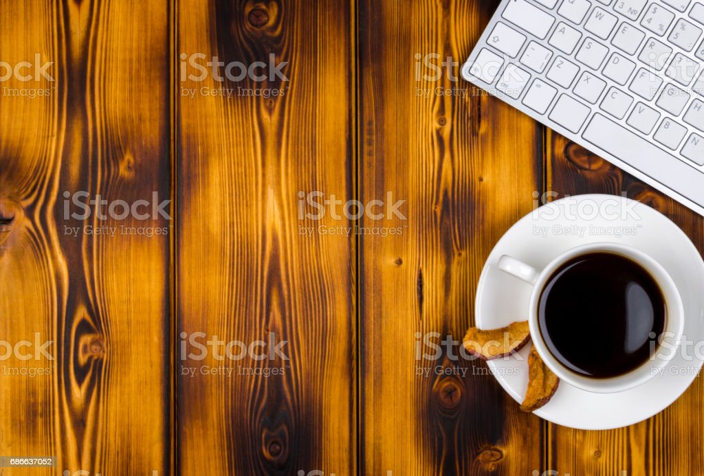 Office desk with copy space. Digital devices wireless keyboard and mouse on burned wooden table with cup of coffee, top view royalty-free stock photo