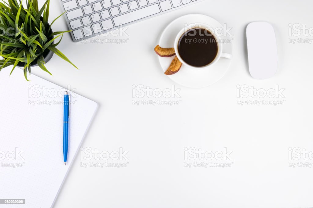 Office desk with copy space. Digital devices wireless keyboard and mouse on office table with notepad and cup of coffee, top view royalty-free stock photo