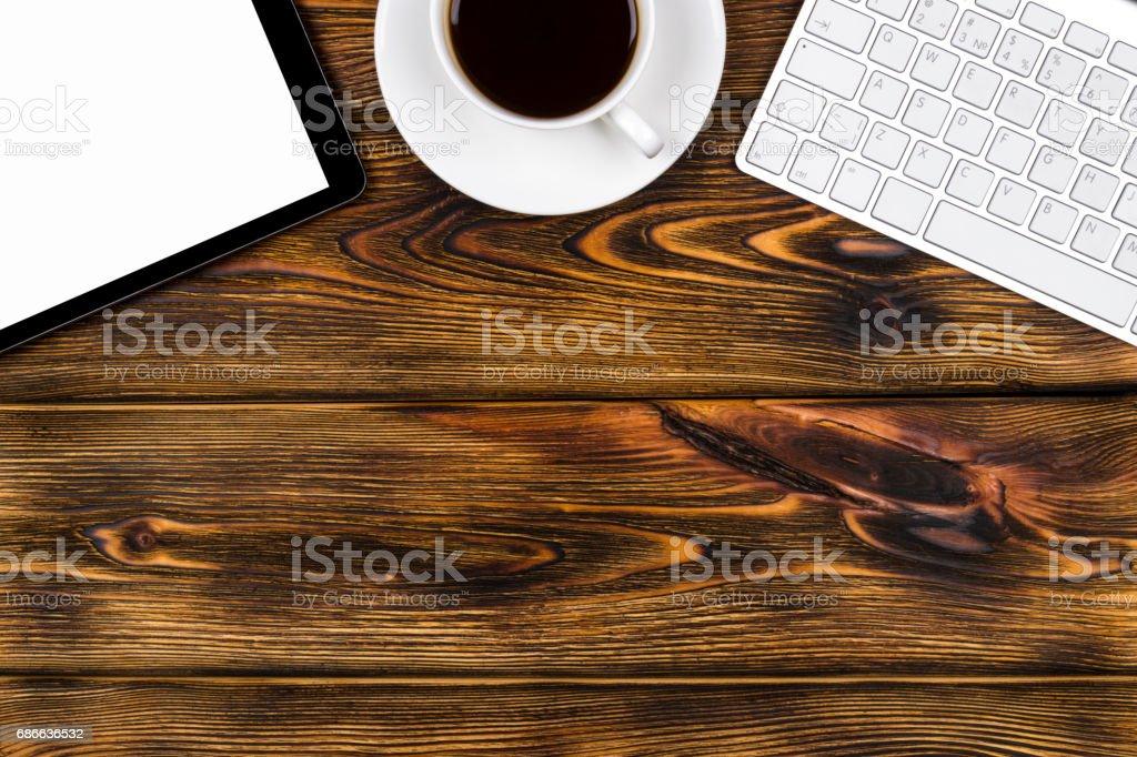 Schreibtisch mit Textfreiraum. Digitale Geräte wireless Tastatur, Maus und Tablet-Computer mit leeren Bildschirm auf gebrannten Holztisch mit Tasse Kaffee, Ansicht von oben Lizenzfreies stock-foto