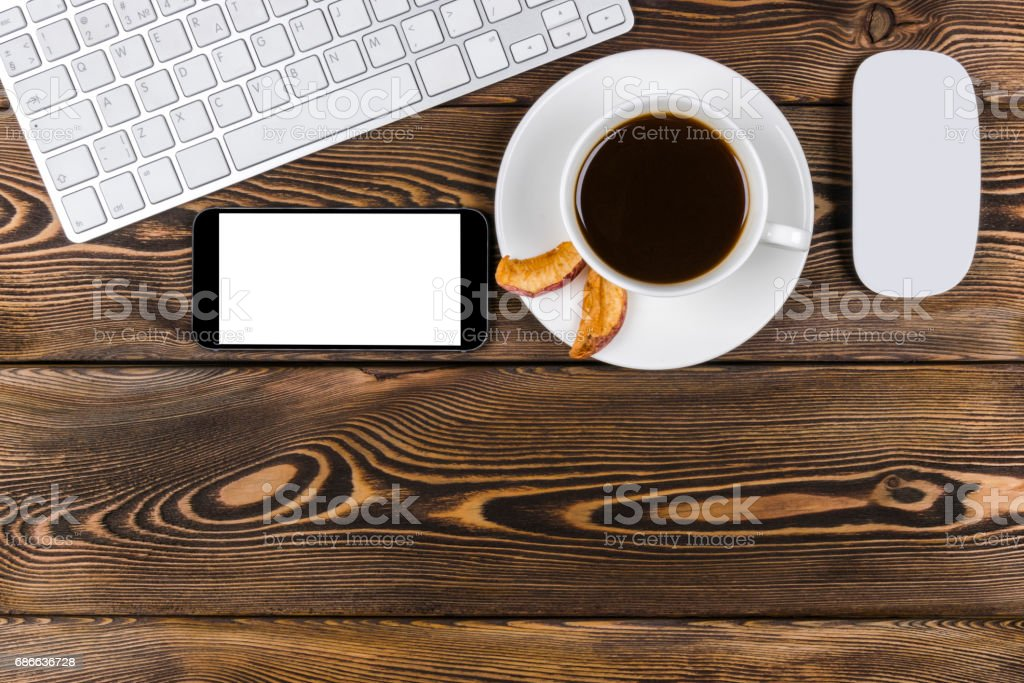 Office desk with copy space. Digital devices wireless keyboard, mouse and smartphone with empty screen on dark  wooden table with cup of coffee, top view royalty-free stock photo