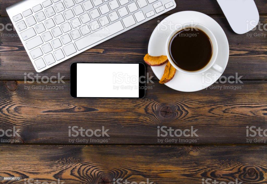 Schreibtisch mit Textfreiraum. Digitale Geräte drahtlos, Tastatur, Maus und Smartphone mit leeren Bildschirm auf dunklen Holztisch mit Tasse Kaffee, Ansicht von oben Lizenzfreies stock-foto