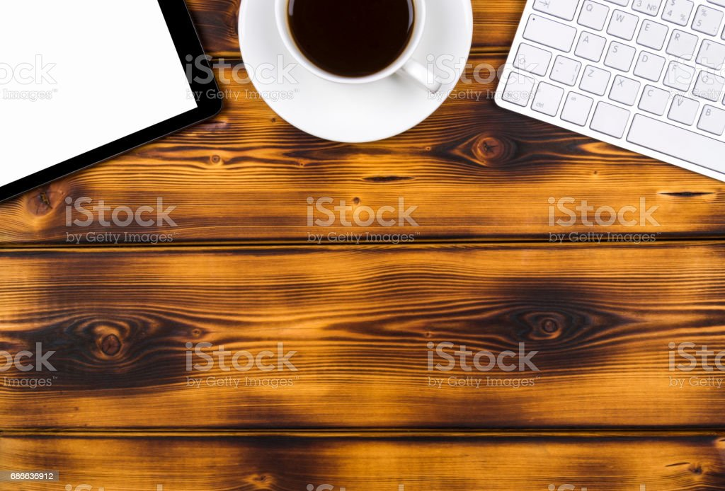 Office desk with copy space. Digital devices wireless keyboard, mouse and tablet computer with empty screen on burned  wooden table with cup of coffee, top view royalty-free stock photo