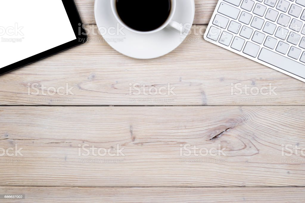 Office desk with copy space. Digital devices wireless keyboard, mouse and tablet computer with empty screen on white  wooden table with cup of coffee, top view royalty-free stock photo