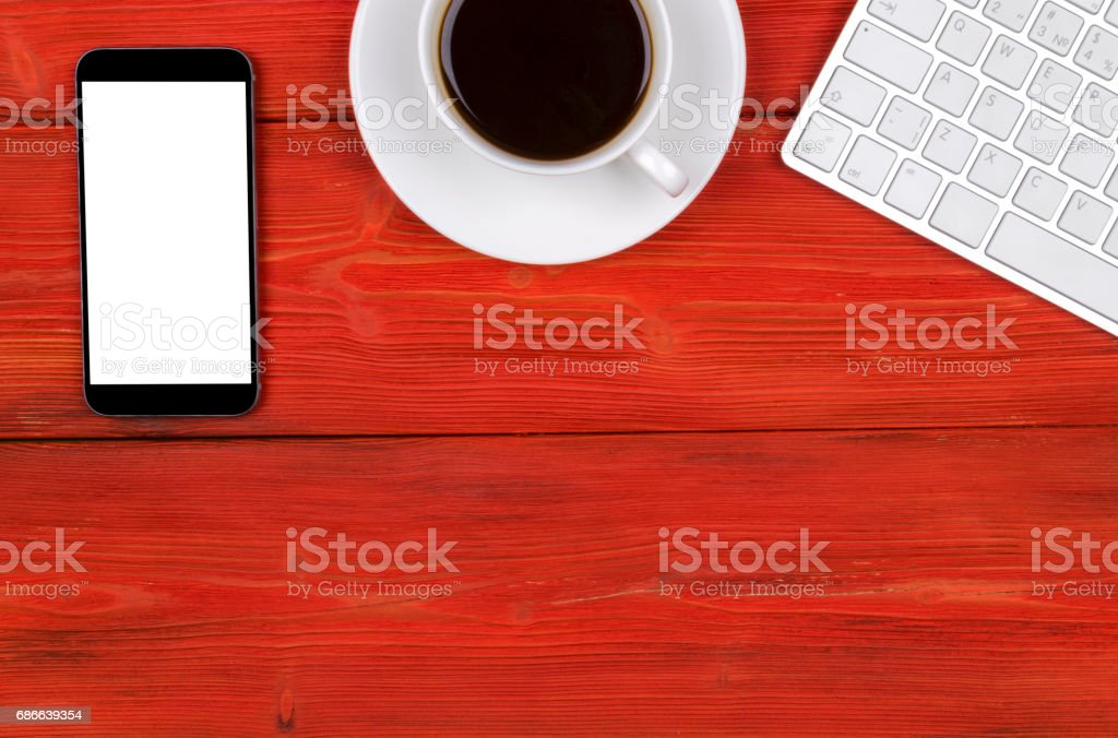 Office desk with copy space. Digital devices wireless keyboard, mouse and tablet computer with empty screen on red  wooden table with cup of coffee, top view royalty-free stock photo