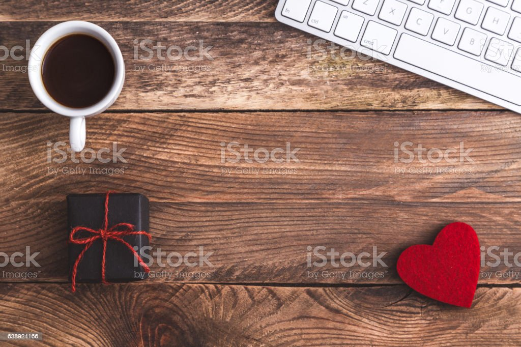 Office desk with gift, keyboard, cup of coffee and felt heart. View...