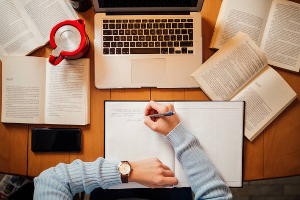 office desk with laptop and books, top view - imparare foto e immagini stock