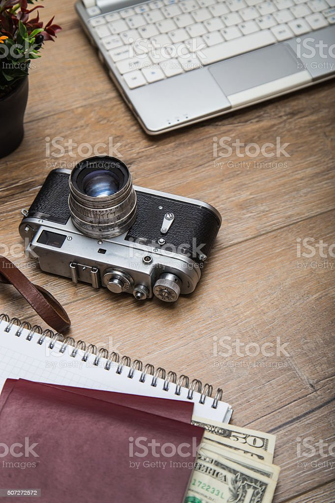 Office desk with laptop, money, passports, notebook and camera stock photo