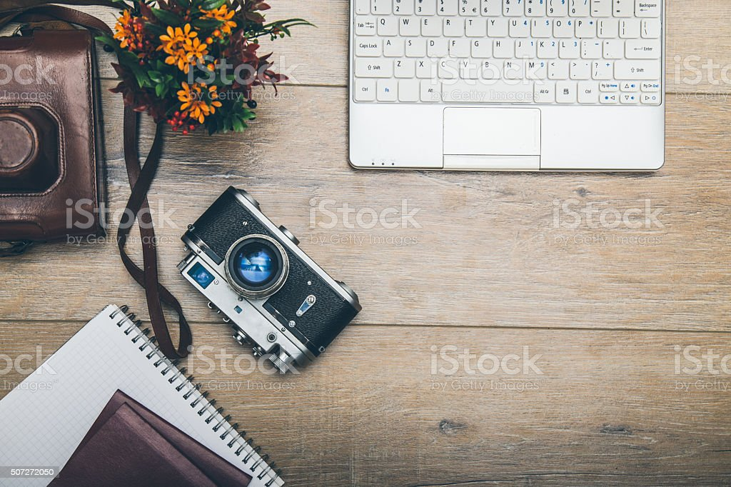 Office desk with laptop, passports, notebook and camera stock photo