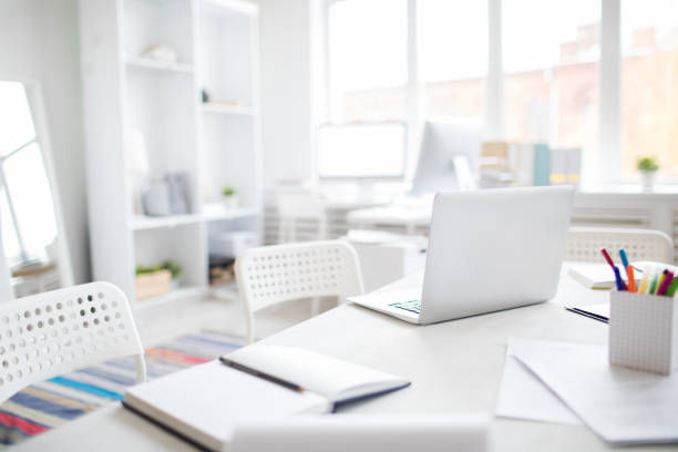 Office desk with laptop Image of office table with laptop, notepad and other office supplies in a modern well-furnished office empty desk stock pictures, royalty-free photos & images