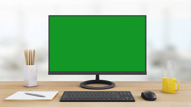 office desk with large pc computer screen with green background - template - green screen background stock photos and pictures