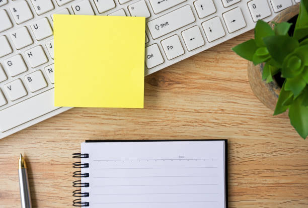 office desk with note pad, computer keyboard, pen and plant - adhesive note stock photos and pictures