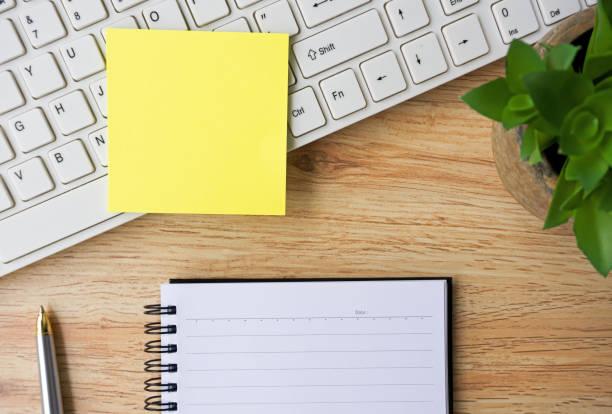 schreibtisch mit notizblock, computer-tastatur, stift und pflanze - klebezettel stock-fotos und bilder