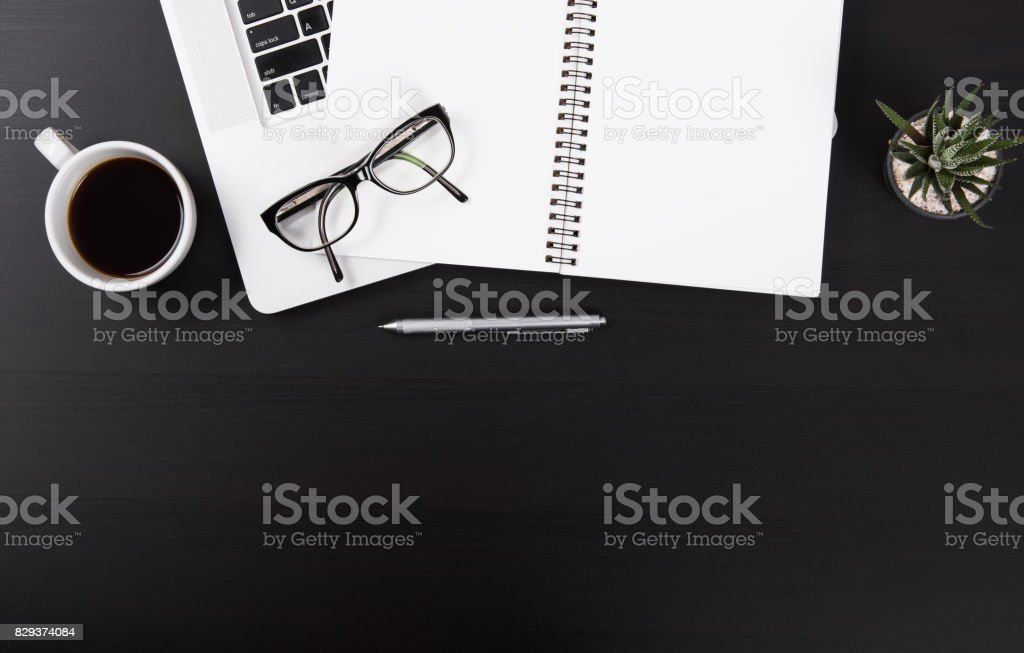 Office desk with notebook,notepad,glasses,computer,cactus and coffee cup.Top View table from above with copy space stock photo