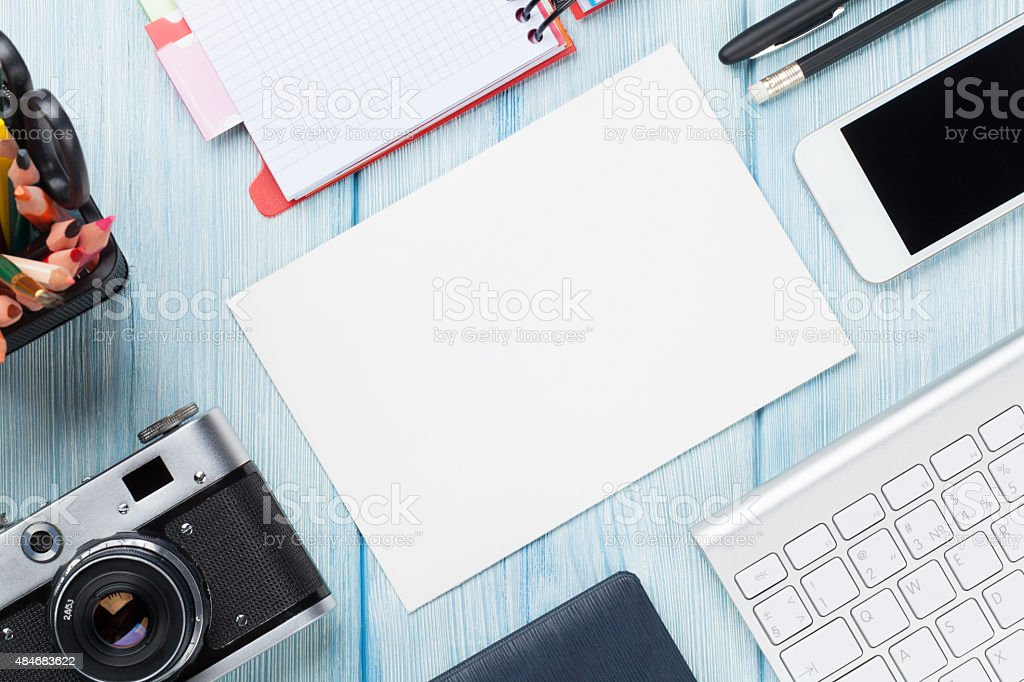Office desk with supplies, camera and blank card stock photo